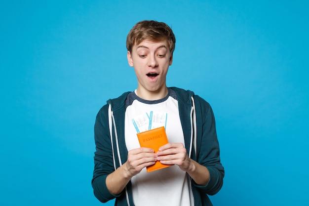 Überraschter junger mann in freizeitkleidung, der den mund weit offen hält, reisepass hält, bordkarte einzeln auf blauer wandwand. menschen aufrichtige emotionen, lifestyle-konzept.