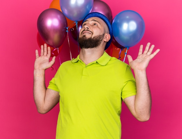 Überraschter junger mann mit blauem partyhut, der vor luftballons steht und die hände ausbreitet
