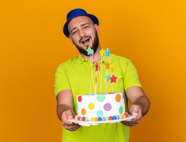 Überraschter junger mann mit partyhut, der kuchen in die kamera hält