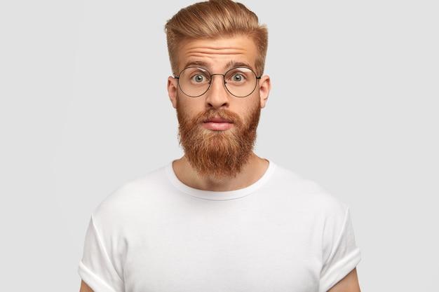 Überraschter junger mann mit trendigem haarschnitt, hat ingwerbart und schnurrbart