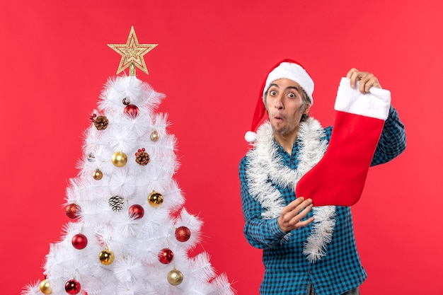 Überraschter junger mann mit weihnachtsmannhut in einem blauen gestreiften hemd und halten weihnachtssocke nahe weihnachtsbaum auf rot