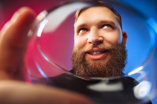 Überraschter junger mann posiert mit einem glas wein. emotionales männliches gesicht. blick aus dem glas.