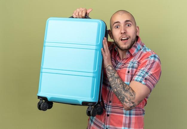 Überraschter junger reisender, der koffer isoliert auf olivgrüner wand mit kopienraum hält