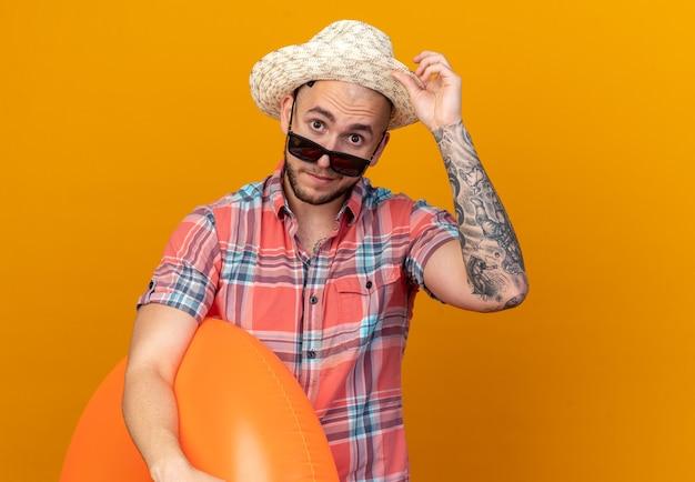 Überraschter junger reisender mann mit strohstrandhut in sonnenbrille, der schwimmring isoliert auf oranger wand mit kopierraum hält