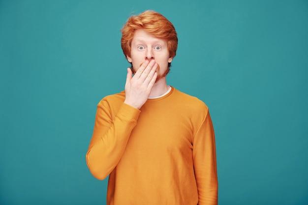 Überraschter junger rothaariger mann im orangefarbenen pullover, der auf blau steht und mund in der aufregung bedeckt