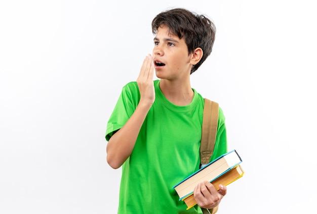 Überraschter junger schuljunge mit rucksack, der bücher hält, bedeckte den mund mit der hand isoliert auf weißer wand