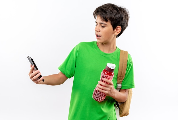 Überraschter junger schuljunge mit rucksack, der eine wasserflasche hält und auf dem telefon in der hand schaut, isoliert auf weißer wand