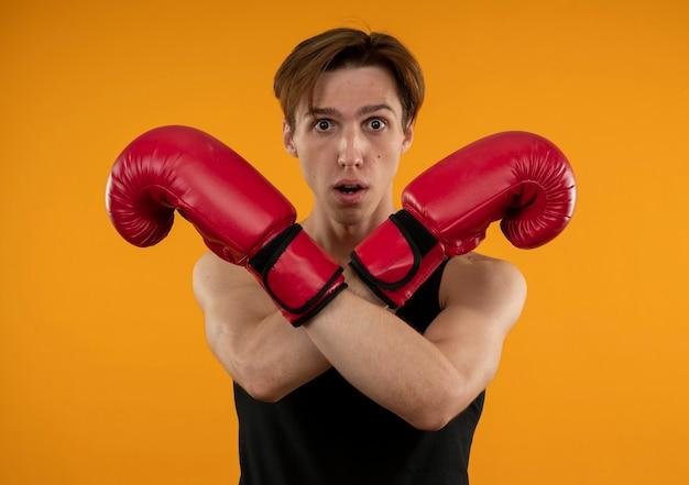 Überraschter junger sportlicher kerl, der boxhandschuhe trägt, die geste des nicht-isolierten auf der orangefarbenen wand zeigen