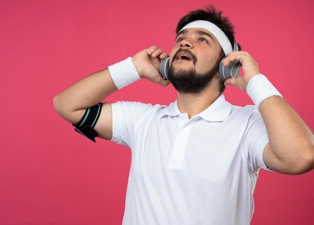 Überraschter junger sportlicher mann, der das tragen des stirnbandes und des armbandes mit kopfhörern und telefonarmband nach oben schaut