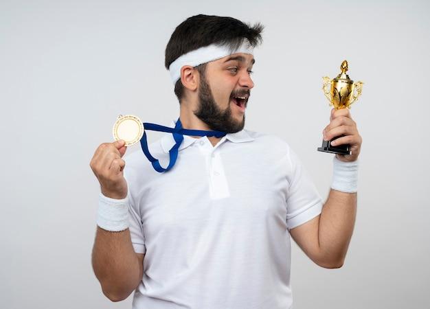 Überraschter junger sportlicher mann, der stirnband und armband mit halten und betrachten des siegerpokals trägt und medaille trägt