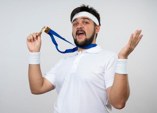 Überraschter junger sportlicher mann, der stirnband und armband mit sich ausbreitenden händen trägt und medaille lokalisiert auf weißer wand trägt