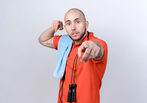 Überraschter junger sportlicher mann mit handtuch auf schulter und springseil auf schulter lokalisiert auf weiß