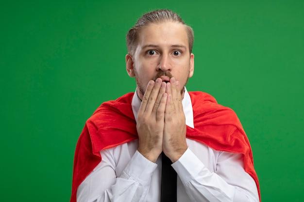 Überraschter junger superheld, der krawatten bedeckten mund mit den auf grün lokalisierten händen trägt