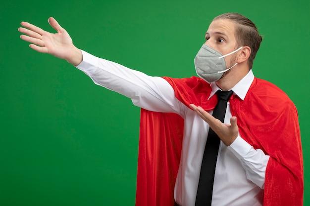 Überraschter junger superhelden-typ, der medizinische maske trägt, die seite und punkte mit händen an der seite lokalisiert auf grünem hintergrund betrachtet