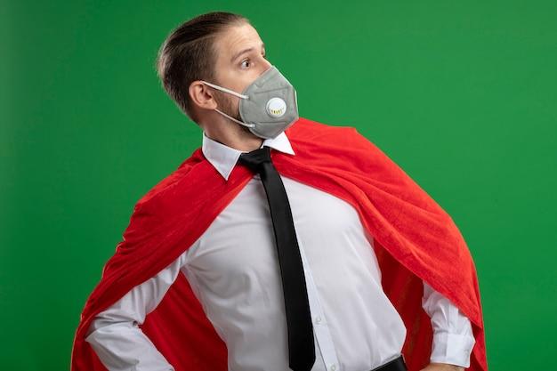 Überraschter junger superhelden-typ, der medizinische maske und krawatte trägt, die seite lokalisiert auf grünem hintergrund betrachtet