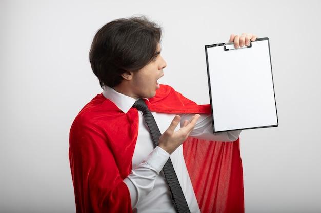 Überraschter junger superheldenmann, der krawattenhaltung und punkte mit hand an zwischenablage trägt, die auf weiß lokalisiert wird