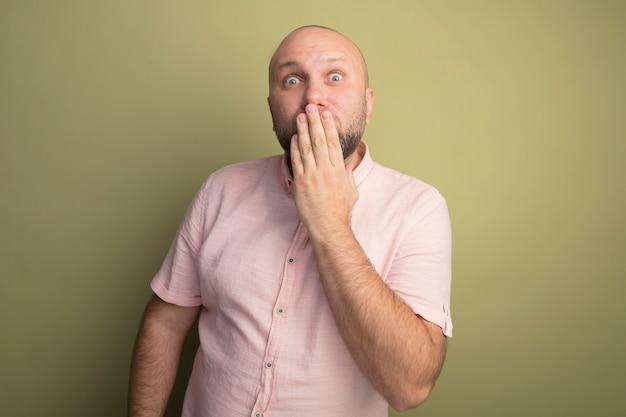 Überraschter kahler mann mittleren alters, der den rosa t-shirt-bedeckten mund mit der hand trägt