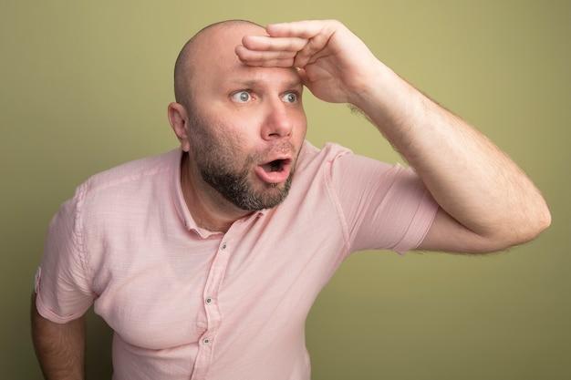 Überraschter kahler mann mittleren alters, der rosa t-shirt trägt, das entfernung mit hand lokalisiert auf olivgrün betrachtet