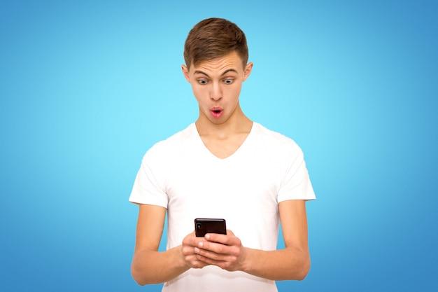 Überraschter kerl im weißen t-shirt mit telefon, isolat, mann auf blauem hintergrund im studio mit telefon