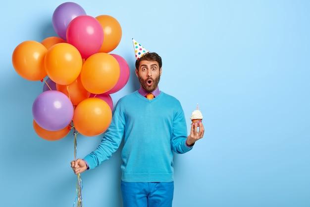 Überraschter kerl mit geburtstagshut und luftballons, die im blauen pullover aufwerfen