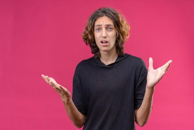 Überraschter kerl mit langen haaren im schwarzen t-shirt breitete seine hände auf rosa hintergrund aus