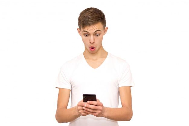 Überraschter kerl mit telefon, isolat, mann auf weißem hintergrund im studio