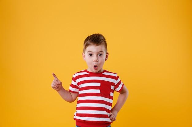Überraschter kleiner junge, der steht und finger weg zeigt