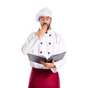 Überraschter koch, der ein buch liest