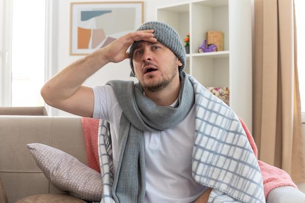 Überraschter kranker slawischer mann mit schal um den hals, der eine in plaid gehüllte wintermütze trägt und die hand auf die stirn legt, die auf der couch im wohnzimmer sitzt