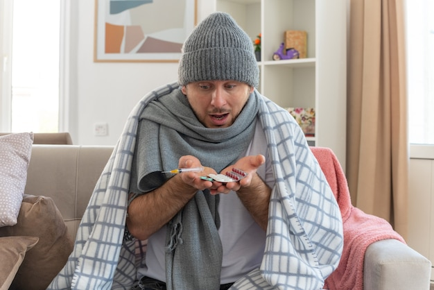 Überraschter kranker slawischer mann mit schal um den hals, der eine wintermütze trägt, die in kariertes halten gewickelt ist und medizinblisterpackungen und spritze auf der couch im wohnzimmer betrachtet