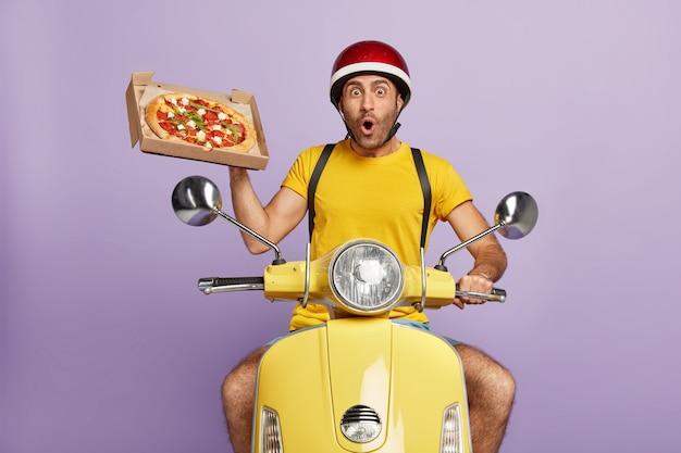 Überraschter lieferbote, der gelben roller fährt, während er pizzaschachtel hält