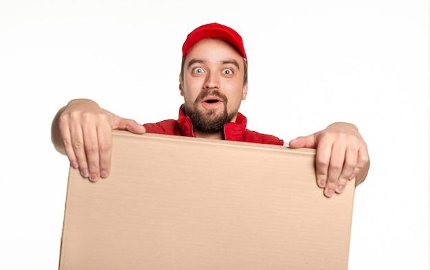 Überraschter lieferbote in roter uniform und mütze, die mit aufgeregtem gesichtsausdruck beim tragen des riesigen pappkartons suchen