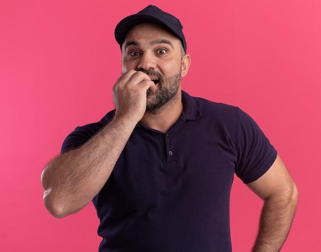 Überraschter lieferbote mittleren alters in uniform und mütze beißt nägel isoliert auf rosa wand