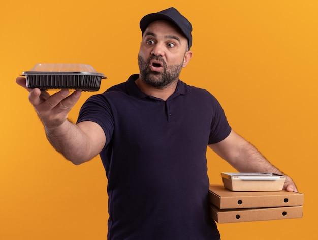 Überraschter lieferbote mittleren alters in uniform und mütze, die pizzaschachteln halten und lebensmittelbehälter heraushalten, der auf gelber wand lokalisiert wird