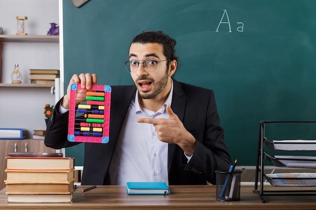 Überraschter männlicher lehrer, der eine brille trägt und auf den abakus zeigt, der am tisch mit schulwerkzeugen im klassenzimmer sitzt