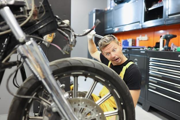 Überraschter männlicher mechaniker, der sich mit dem schraubenschlüssel den kopf kratzt und das motorrad betrachtet. schwierigkeiten bei der arbeit des automechaniker-konzepts