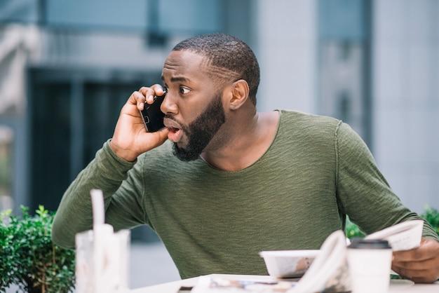 Überraschter mann, der am telefon spricht