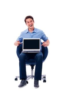 Überraschter mann, der auf laptop zeigt