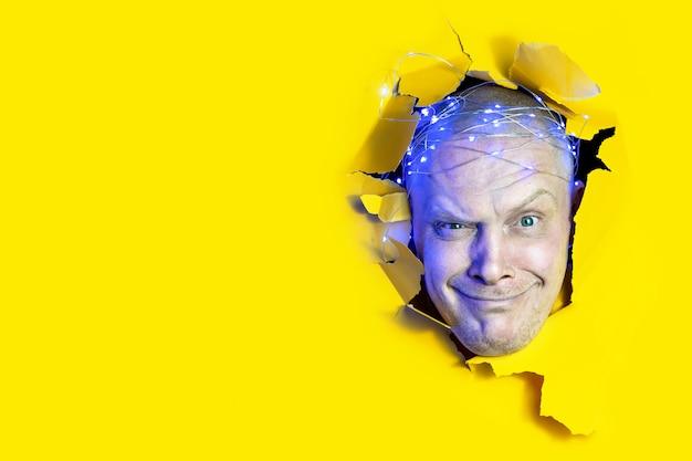 Überraschter mann, der durch loch im gelben papierhintergrund schaut