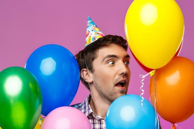 Überraschter mann, der geburtstag feiert und bunte luftballons über lila wand hält.
