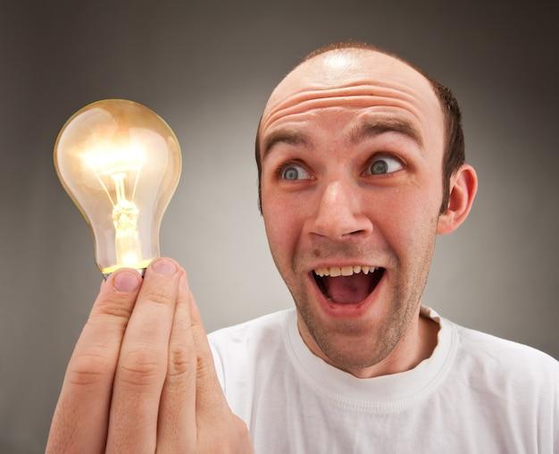 Überraschter mann, der glühbirne hält