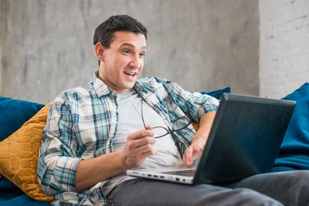 Überraschter mann, der laptop auf sofa verwendet