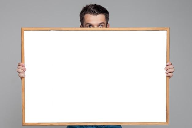 Überraschter mann, der leeres weißes brett zeigt