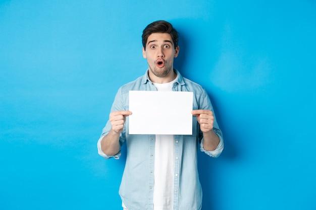 Überraschter mann, der nach luft schnappt und beeindruckt in die kamera schaut, ein leeres blatt papier für ihr schild zeigt und auf blauem hintergrund steht