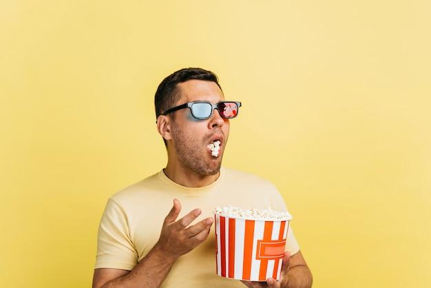 Überraschter mann, der popcorn mit kopienraum isst