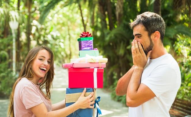 Überraschter mann, der seinen freundinholdingstapel geschenke betrachtet