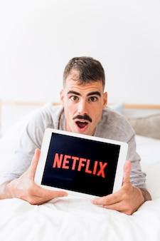 Überraschter mann, der tablette mit netflix-logo zeigt