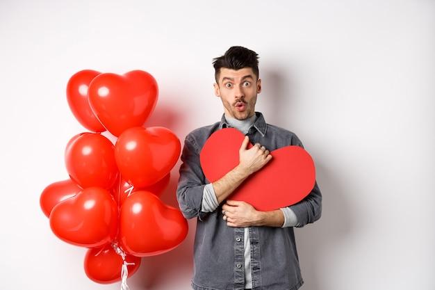 Überraschter mann, der valentinsherzkarte hält und wow sagt, erstaunt in die kamera schaut, erhält geheimes geständnis am tag des liebenden, das nahe romantischen luftballons auf weiß steht.