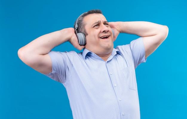 Überraschter mann des mittleren alters im blau gestreiften hemd, das kopfhörer trägt, die musik auf einem blauen hintergrund genießen