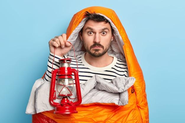Überraschter mann hat ruhe, in schlafsack gewickelt, hält petroleumlampe, genießt erholung im wald, hat expedition, posiert gegen blaue wand
